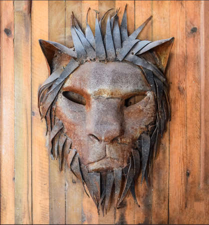 The face of a lion made of metal on a wooden canvas.