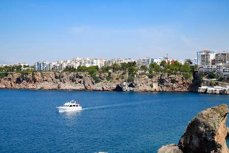 Antalya, Turkey - May 19, 2019: The yacht sails along the rocky coast, an excursion along the coast of Antalya.