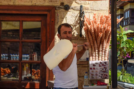 Antalya, Turkey - May 19, 2019: The ice cream seller is spinning ice cream on a stick. Redactioneel