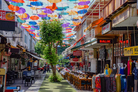 Antalya, Turkey - May 19, 2019: Street in Kaleici with umbrellas suspended between buildings.