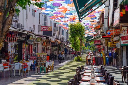 Antalya, Turkey - May 19, 2019: Street in Kaleici with umbrellas suspended between buildings.
