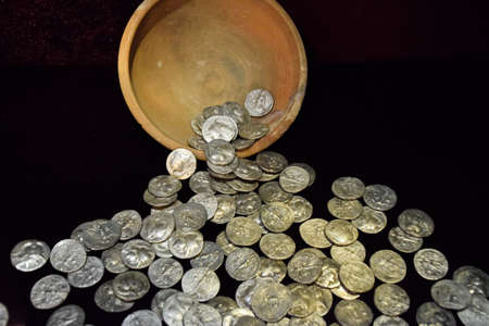 Silver coins poured out of a clay pot