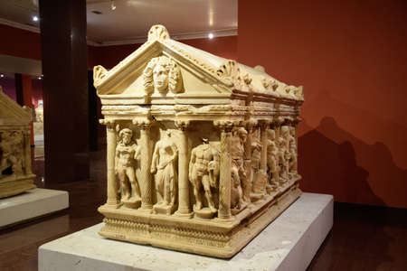 Antalya, Turkey - May 20, 2019: Marble sarcophagus. Sarcophagi from the excavations of the city of Perge. Scenes and symbols carved in the bas-relief on the walls of the sarcophagus. Museum of antiquity of Antalya.