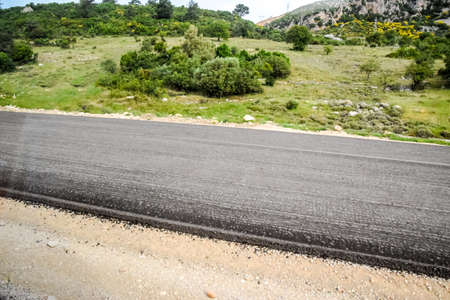 道路上の新しいアスファルトを敷設。新しい道と新しいアスファルト。
