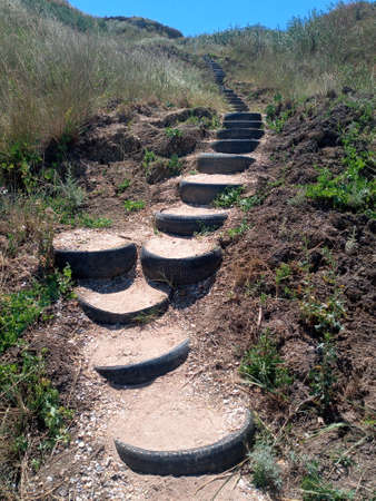Steps to the top of the hill, made of car treads. Creative from old car wheels. Road to the mountain. Imagens