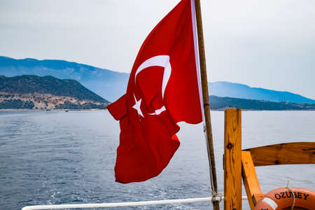 The flag of Turkey flutters in the wind on the deck of a pleasure yacht.