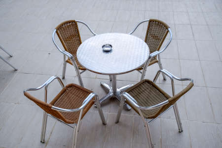 Metal tables and chairs with wicker seats in an outdoor cafe. Stockfoto - 127922252