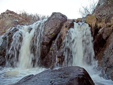 Waterfall from the thawed waters. Melting snow in the hilly tundra. Waterfall