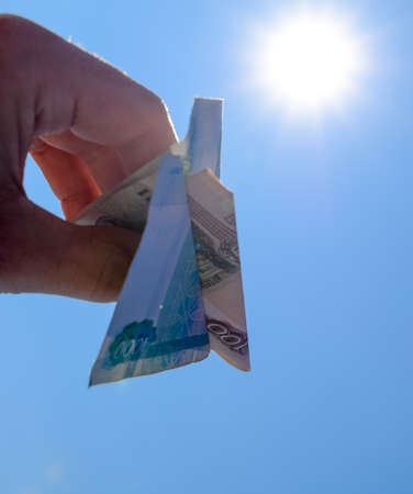 Denominations of Russian money, folded in the airplane against the blue sky in hand.