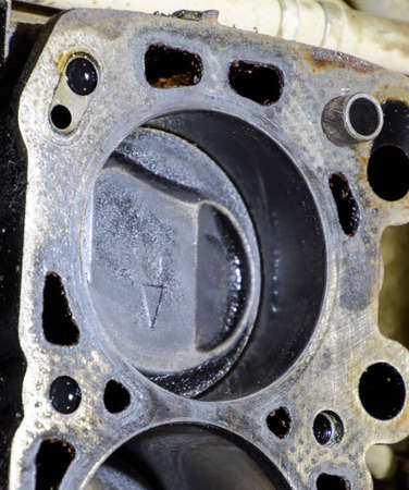 The cylinder block of the four-cylinder engine. Disassembled motor vehicle for repair. Parts in engine oil. Car engine repair in the service.