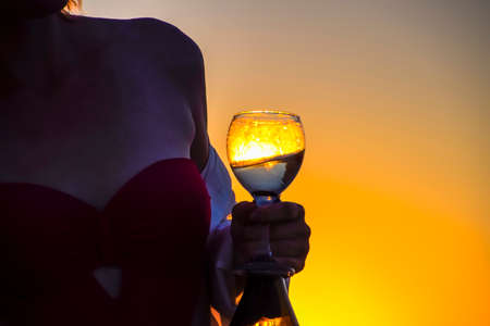A glass of champagne in the hands of a woman on the seashore on a sunset background.