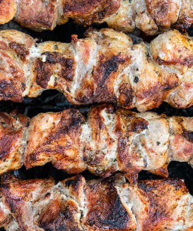 Frying pork on a skewer over a brazier. Turning meat over coals. Appetizing shish kebab. Delicious barbecue.