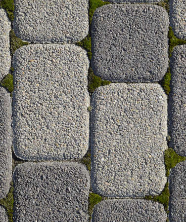 Industrial building background of paving slabs with overgrown with moss in the cracks. Texturing background.