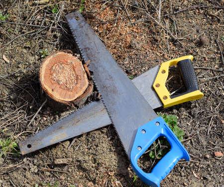 Two saws hacksaws lie across. Garden tool saw. Two saws hacksaws lie across
