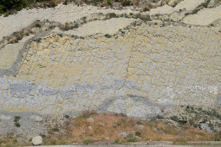 slope of the mountain with layers of sedimentary rocks. Vertically located sedimentary rocks on a collapsing hillside.