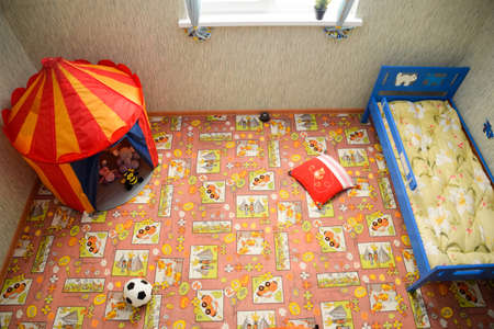 Novorossiysk, Russia - May 20, 2018: Childrens room, top view. Toys on the floor and a crib in the corner.