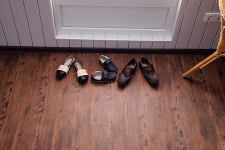 Shoes near the door in the hallway. Hallway in the house.