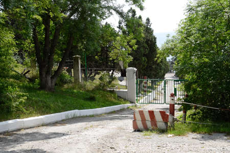 The gate of the summer house of a corrupt official on the seashore. The thug general built his country house and put up a fence.