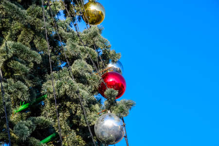 Tinsel and toys, balls and other decorations on the Christmas Christmas tree standing in the open air. Decorations New Year tree.