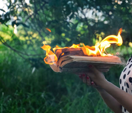 Burning book in the hands. Burning books in the forest. The girl holds a burning book in her hands. A young woman in a forest burns a book. Фото со стока