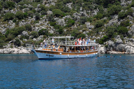 Demre, Turkey - May 21, 2019: Tourists swim in the sea near a pleasure yacht. The Mediterranean Sea off the coast of Kekova and Demre. Many vacationers are swimming in the Mediterranean Sea near the cruise boat. Éditoriale