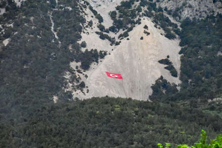 Antalya, Turkey - May 21, 2019: Flag of Turkey drawn on the rocks. Cliff with the flag of Turkey. Éditoriale