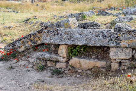 Fragments of ancient buildings, the ruins of the ancient city of Hierapolis. Stone blocks with traces of stone machining. Stock Photo