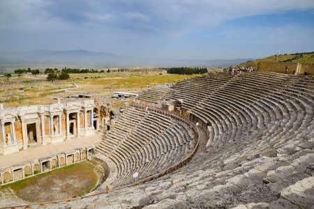 Pamukkale, Hierapolis, Turkey - May 22, 2019: Ancient antique amphitheater in the city of Hierapolis in Turkey. Steps and antique statues with columns in the amphitheater Standard-Bild - 133523216