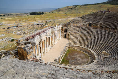 Pamukkale, Hierapolis, Turkey - May 22, 2019: Ancient antique amphitheater in the city of Hierapolis in Turkey. Steps and antique statues with columns in the amphitheater Redakční