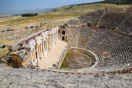 Pamukkale, Hierapolis, Turkey - May 22, 2019: Ancient antique amphitheater in the city of Hierapolis in Turkey. Steps and antique statues with columns in the amphitheater Editorial