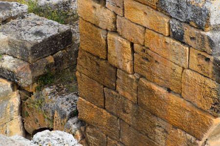 The remains of the ancient antique buildings of Hierapolis from limestone blocks, dilapidated walls. Stock Photo
