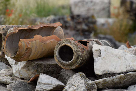 The remains of ancient ceramic pipes from the water supply. Prefabricated sections of ceramics from which the pipeline was assembled. Stock Photo