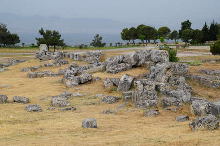 Fragments of ancient buildings, the ruins of the ancient city of Hierapolis. Stone blocks with traces of stone machining. 免版税图像