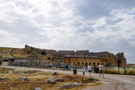 Pamukkale, Hierapolis, Turkey - May 22, 2019: Tour groups on the ruins of Hierapolis. Tourists are shown the ruins of the ancient city.