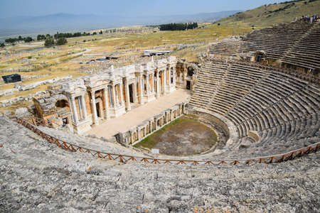 Pamukkale, Hierapolis, Turkey - May 22, 2019: Ancient antique amphitheater in the city of Hierapolis in Turkey. Steps and antique statues with columns in the amphitheater 新闻类图片