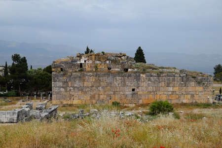 The remains of the ancient antique buildings of Hierapolis from limestone blocks, dilapidated walls. 免版税图像