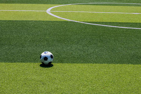 The old soccer football on the white line in the artificial turf