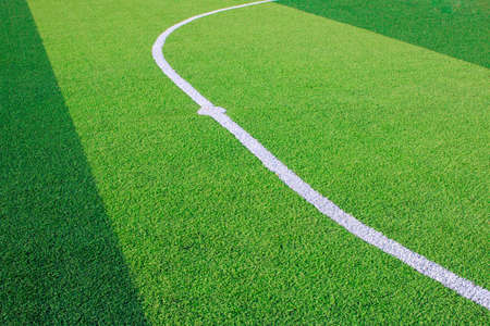 Photo of a green synthetic grass sports field with white line shot from above. Stock Photo