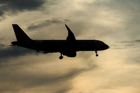 Silhouette passenger airplane flying away in to sky high altitude on sunset