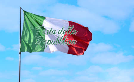 Italian flag flying in a blue light sky. Italian fly with the text: Festa della Repubblica. Photo relate to a National public holiday in Italy. Real flag. Photo with copy space.