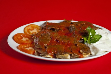 Traditional turkish iskender kebab served on white plate with vegetables mix photo