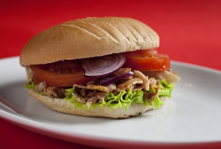 Traditional turkish doner kebab in bread served on white plate photo