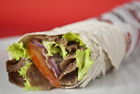 Traditional turkish doner kebab in lavash bread served on white plate Stock Photo