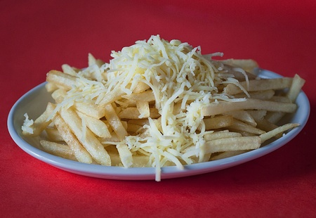 chese: Crunchy french fries with chese on a white plate