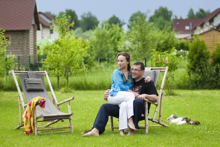 Portrait of happy couple sinnting together in one deck chairs photo