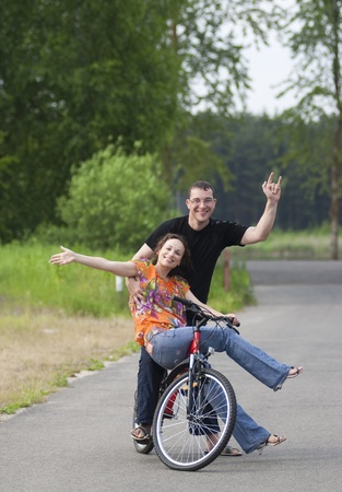 Happy couple sitting together at one bicycle photo