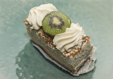 a portion: Portion of cake with kiwi and cream Stock Photo