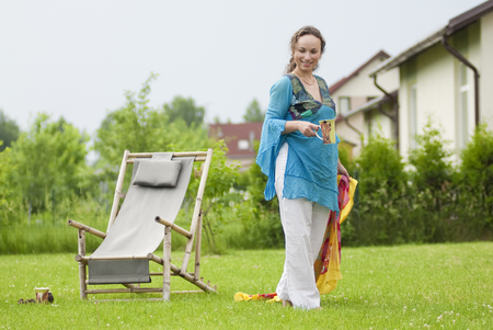 Cute woman with cup near a deck chair