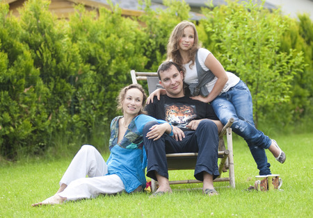 summerhouse: Portrait of parents with teenager daughter relaxing on nature Stock Photo