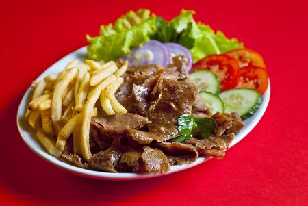 pinchos morunos: Kebab tradicional doner turco servido en plato blanco con patatas y vegetal mezcla